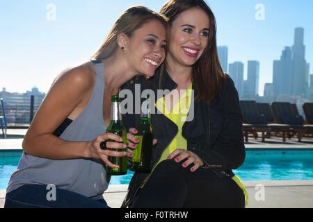 Portrait of two young female friends drinking beers at rooftop bar with Los Angeles skyline, USA - Stock Photo