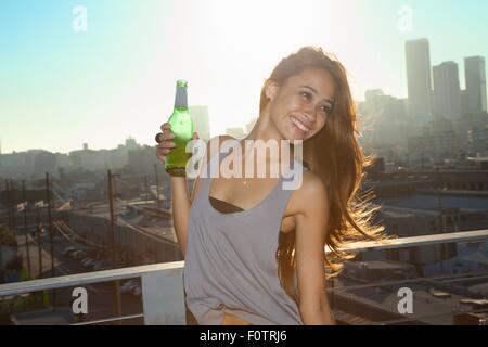 Portrait of young woman drinking beer on rooftop bar with Los Angeles skyline, USA - Stock Photo