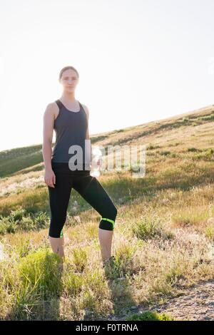 Portrait of young female runner on hillside with bottle of water - Stock Photo