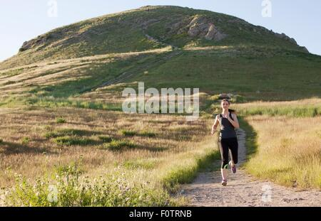 Young woman running on hillside track - Stock Photo