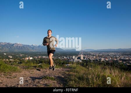 Young male runner running along track above city in valley - Stock Photo
