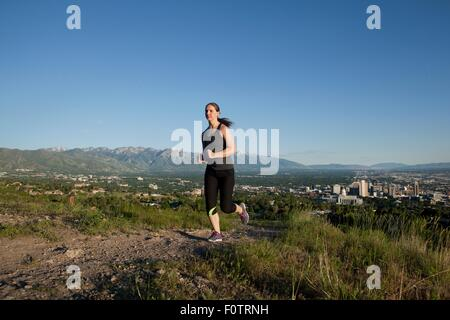 Young female runner running along track above city in valley - Stock Photo
