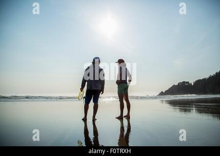 Rear silhouetted view of two young men chatting on Short Sands Beach, Oregon, USA - Stock Photo