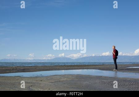 Side view of young man standing at waters edge looking out, Great Salt lake, Utah, USA - Stock Photo