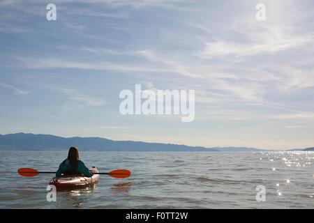 Rear view of young woman kayaker sitting in kayak on water, Great Salt Lake, Utah, USA - Stock Photo