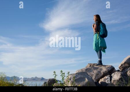 Rear view of young woman wearing backpack standing on rocks looking away, Great Salt Lake, Utah, USA - Stock Photo