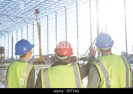 Rear view of surveyor and builders meeting on construction site - Stock Photo