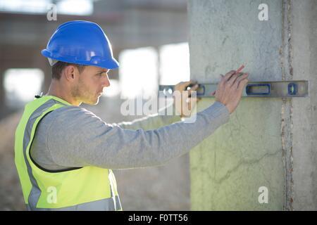 Surveyor using spirit level on construction site pillar - Stock Photo