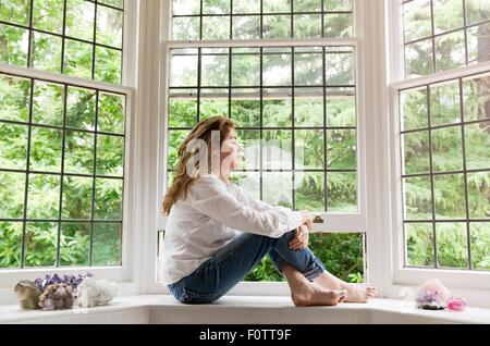 Portrait of mature woman sitting on living room windowsill looking out of window - Stock Photo