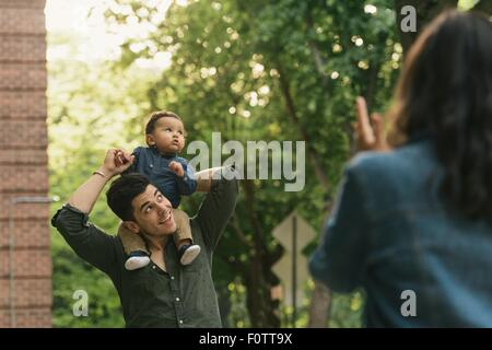 Baby boy sitting on fathers shoulders, looking away curiously - Stock Photo