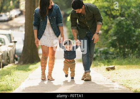 Front angle view of mother and father holding baby boys hands while walking - Stock Photo