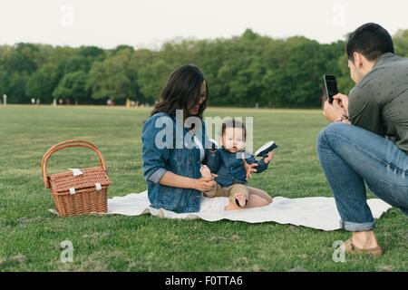 Father using smartphone to photograph mother and baby boy sitting on blanket - Stock Photo