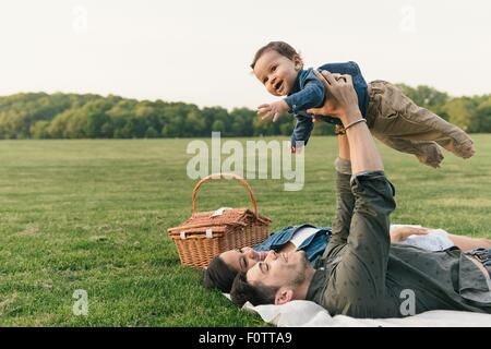 Mother and father laying on backs raising baby boy into the air - Stock Photo