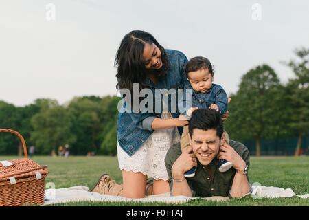 Mother steadying baby boy sitting on fathers shoulders, pulling hair - Stock Photo