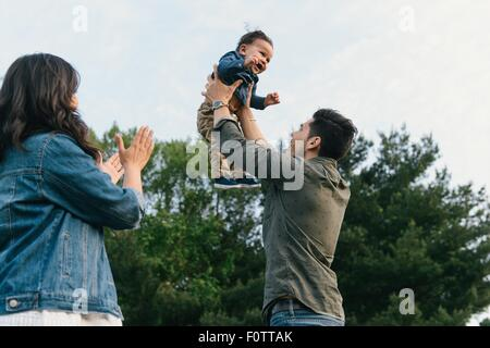 Low angle view of father throwing baby boy into air playfully - Stock Photo