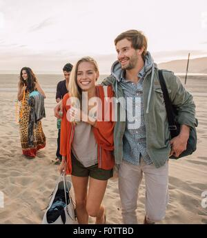 Group of friends walking along beach, young couple looking at smartphone