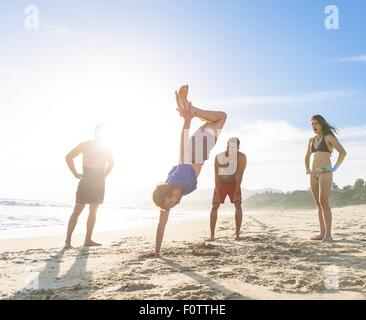 Group of friends on beach watching friend do handstand - Stock Photo