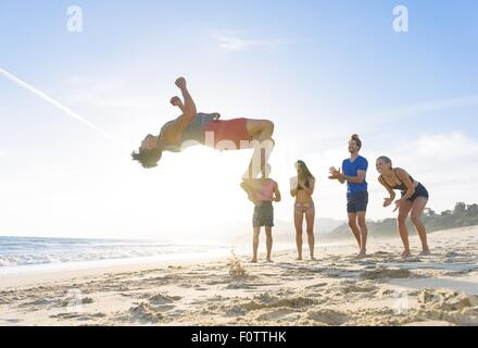 Group of friends on beach watching friend do somersault - Stock Photo