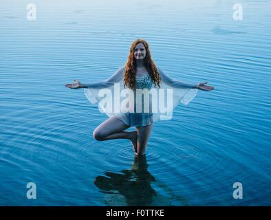 Young woman standing in blue lake practicing yoga - Stock Photo