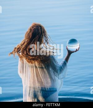 Rear view of young woman with long red hair standing in lake holding crystal ball - Stock Photo