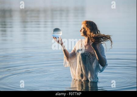 Young woman with long red hair standing in lake gazing at crystal ball - Stock Photo