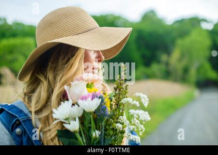Portrait of young woman with bunch of flowers and wearing straw hat - Stock Photo