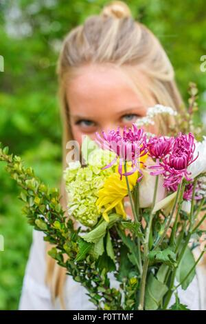 Portrait of young woman behind bunch of flowers - Stock Photo