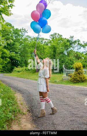 Young woman gazing up at bunch of balloons on rural road - Stock Photo