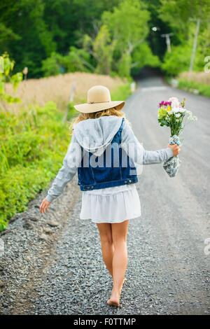 Rear view of bare footed young woman walking on rural gravel road carrying bunch of flowers - Stock Photo