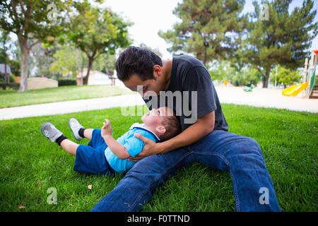 Male toddler playing with older adult brother in park - Stock Photo