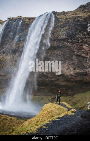 Female tourist at Seljalandsfoss waterfall, Iceland - Stock Photo
