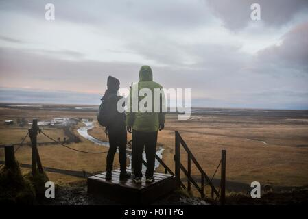 Male and female tourists taking photographs from viewing platform at Seljalandsfoss, Iceland - Stock Photo