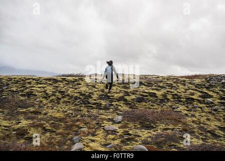 Rear view of female tourist running across moorland,  Skaftafell, Iceland - Stock Photo