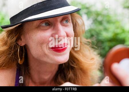 Close up portrait of blue eyed mid adult woman with red hair - Stock Photo