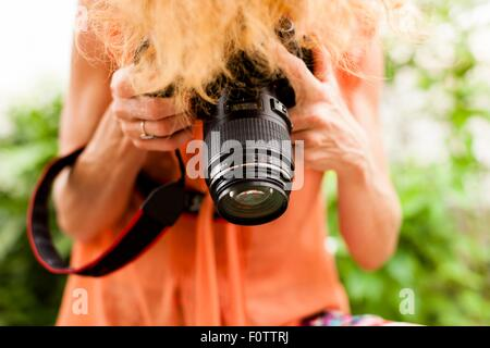 Cropped shot of woman with red hair photographing downward with digital SLR - Stock Photo