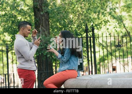 Mid adult man taking smartphone photograph of girlfriend in city park - Stock Photo
