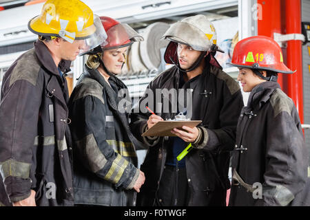 Team Of Firefighters Discussing Over Clipboard - Stock Photo