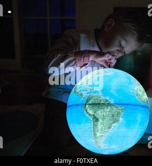 Young boy looking at illuminated globe in dark room - Stock Photo