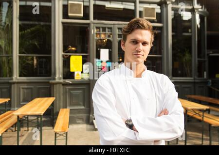 Young chef standing outside of work, arms folded - Stock Photo