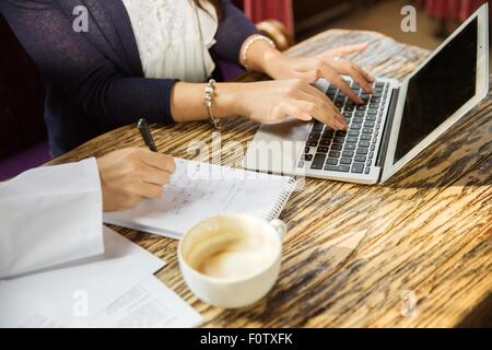 Close up of couples hands using laptop, writing, cropped - Stock Photo