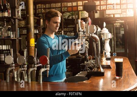 Young man working in public house, serving drinks - Stock Photo