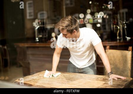 Young man cleaning table in public house - Stock Photo