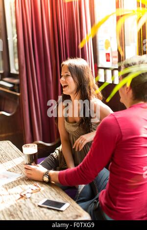 Couple sitting together laughing enjoying a drink - Stock Photo