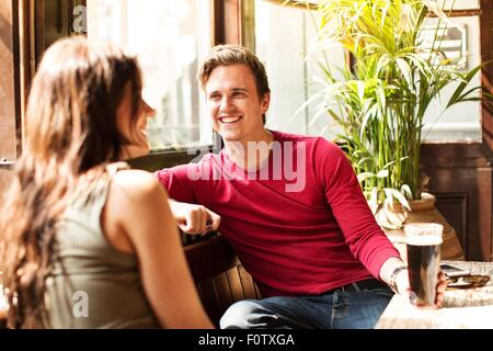 Couple sitting together smiling enjoying a drink - Stock Photo