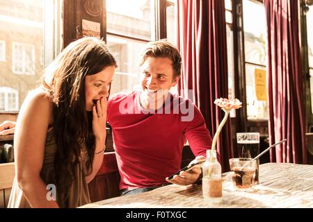 Couple using smartphone together, hand covering mouth - Stock Photo