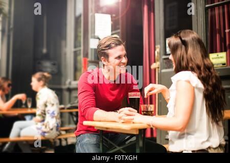 Couple sitting face to face in beer garden holding hands - Stock Photo