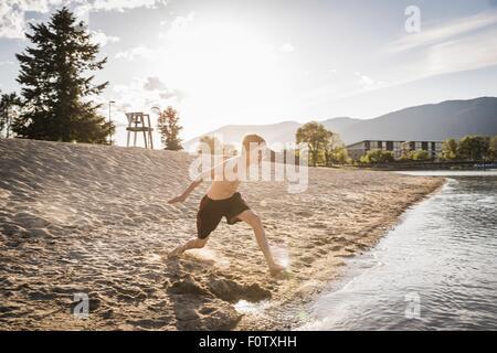 Teenage boy running to waters edge on beach, Sand Point, Idaho, USA - Stock Photo