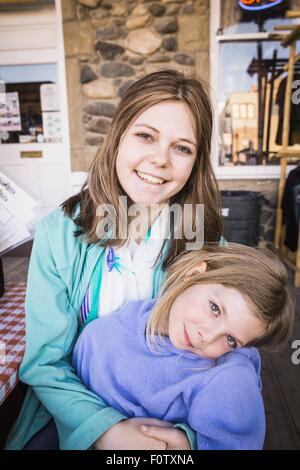 Young woman and girl smiling towards camera, portrait - Stock Photo