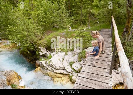 Mature woman with son sitting on wooden footbridge, Bovec, Soca, Slovenia - Stock Photo