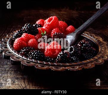 Succulent, juicy, fresh raspberries and blackberries on carved ornamental plate - Stock Photo